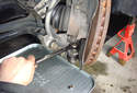 This picture illustrates the front of the left side wheel well, behind the brake rotor at the spindle.