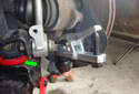 Place a floor jack under the control arm to support the suspension (green arrow).