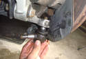 Twist the ball joint away from the lower control arm and pull it out of the bottom of the spindle.