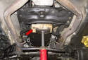 Place a screw jack or hydraulic jack under the transmission with a wood block (red arrow).