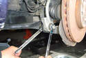 With two 18mm wrenches, remove the sway bar link fasteners at the sway bar.