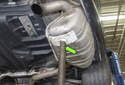 Support the exhaust system from below using a hydraulic floor jack or jack stand (green arrows).