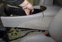 Slide the center console toward the rear of the vehicle and lift it slightly.
