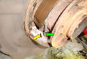 Bring the two shoes together and unhook the parking brake shoe return spring (green arrow) out of the slot for it in the brake shoe (yellow arrow).