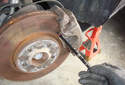 Using a depth measurement tool seat the red ring of the tool on the back of the brake pad at the exposed pad in the caliper.