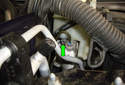 Working below the brake fluid reservoir, remove the T25 Torx fastener (green arrow) for the brake fluid reservoir.