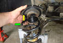 Lift the upper shock absorber mount off of the shock absorber.