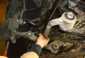 Pull the lower control arm out of the body of the car and lift the outer end of it off the lower ball joint.