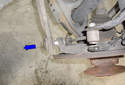 Remove the rear rearward lower link outer mount fastener from the spindle by moving it in the direction of the blue arrow.