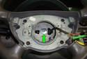 Locate the steering wheel fastener (green arrow).