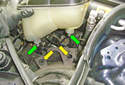 Pull up on the coolant reservoir until you have unseated the two tabs (green arrows) from the rubber mounting grommets (yellow arrows).
