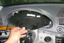 Pull the instrument cluster out of the opening by pulling the top out first.