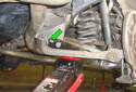 Remove the lower control arm inner mount fastener already removed here (green arrow).