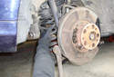 Remove the rear coil spring from the lower control arm of the car.