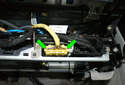 Unplug the airbag seat occupancy sensor connector by squeezing the two locking tabs (green arrows) and pulling the connector away from the seat assembly.