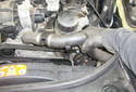 Lift the upper radiator hose out of the plastic holder on the oil filter housing.