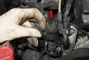 Secondary air solenoid replacing: Move the plastic retaining tab away from the solenoid to the right side of the engine and hold it while lifting the solenoid in the direction of the red arrow.