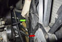 Working at the left side of the cooling fan (red arrow), pull the coolant hose (green arrow) out of the mounts.