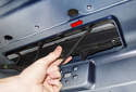Third Brake Light: Pull the LED assembly down and away from the trunk and slide it to the right (red arrow).