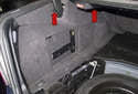 Next, working at the left side carpet trim panel, remove the two plastic rivets (red arrows).