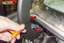Working along the bend of the trunk support trim, use a small flathead screwdriver and unhook the catches (red arrow).