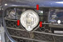 With the trim piece removed use a Philips head screwdriver and remove the three Philips head screws (red arrows) holding the fog light to the bumper cover.