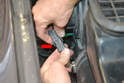 Begin by reaching down on the left side and pulling the blower motor electrical connection off and then separate it by squeezing in the tabs (red arrow) and pulling it apart.