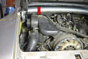 The blower motor assembly is located on the left side of the engine (red arrow).