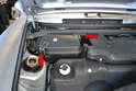 Before you start working on the fuel system let the car cool, then pull back the carpet in the front by the right side A-pillar and release the two clips on the fuse/relay panel cover (red arrows) and remove it.
