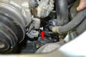 There is a 13mm tensioning bolt and locking nut on the lower right side of the compressor (red arrow), loosen this bolt.