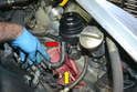 With all the fluid you can get sucked out from the top removed place a few rags under the reservoir (yellow arrow); even though you have removed the fluid some will still be in the bottom of the reservoir and spill out.