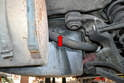 There is also a screw up behind the mufflers on each side that you will need to remove (red arrow).