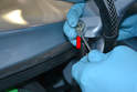 Gently pry the retaining clip off the top of the shock (red arrow) and remove the pin.