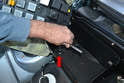 Use a 10mm socket or wrench and remove the bolt holding the bottom of the fuse panel housing to the chassis (red arrow).