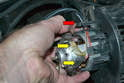 Turn the motor over without stressing the wiring and remove the harness from the grommet (red arrow) and disconnect the wiring (yellow arrows).