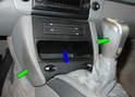 Begin removing the front center console by removing the two side trim panels on either side of the storage box: they simply pull off with a bit of force (green arrows).