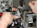 Using your left hand, push the camshaft into place while affixing the camshaft bearing cap into place.