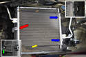 On the 997 the air conditioning condenser is mounted to the front of the radiator buy one bolt on the outside (red arrow) and buy two clips that it sits in on the inside (blue arrows and insert upper right).