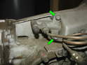 Shown here are the two 13mm bolts (green arrows) that hold the clutch slave cylinder to the transmission.