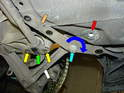 The front control arm (white arrow) is attached to a boomerang-shaped plate (orange arrow) that is bolted to the bottom of the chassis.