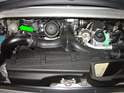 The fuel filter is attached to the coolant reservoir on the left side of the engine compartment (green arrow).
