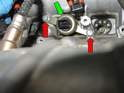 Next, remove the two 10mm bolts (red arrows) that hold the solenoid-retaining bracket (green arrow) to the cylinder head, and remove the retaining bracket.