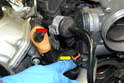 Lift the solenoid for the EVAP line beside the throttle body up and off its mount (red arrow), and disconnect the electrical connection (yellow arrow).