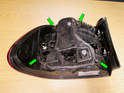 Remove the four securing nuts (green arrows) to release the bulb holder from the taillight housing.