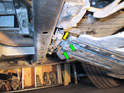 Here is a close-up of the two spring clips (green arrows) that slide through the under tray at the rear as well as the hook on the rear of the tray (yellow arrow) Push the hook up off the support bar and then slide the tray off the two spring clips to remove it.