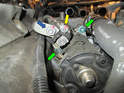 The first step is to remove the 10mm nut (yellow arrow) and the 13mm nut (blue arrow) holding the electrical leads to the starter solenoid.