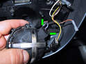 Carefully pry open the two locking tabs on the motor (green arrows) and pull the electrical connector out.