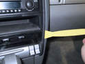 Begin by prying out the trim ring along the perimeter of the center dashboard with a plastic pry bar.