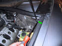After supporting the hood, use a flat head screwdriver to carefully pry the lower end of the hood shock off the ball pivot (green arrow).