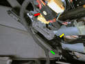 Pull the grommet (green arrow) holding the seat wiring harness to the seat (yellow arrow).